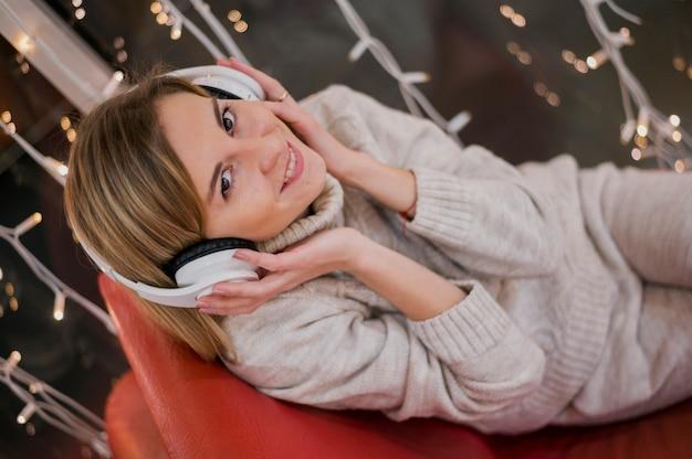 Lächelnde frau, die kopfhörer auf kopf hält und auf couch nahe weihnachtslichtern sitzt Kostenlose Fotos