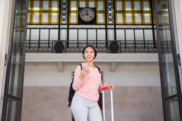 Lächelnde frau, die mit koffer in der stationshalle steht Kostenlose Fotos