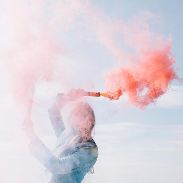 Lächelnde frau, die rote rauchbomben hält Kostenlose Fotos