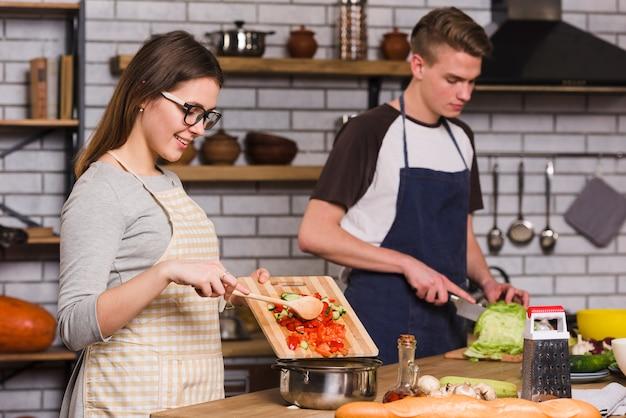 Lächelnde frau, die salat mit freund kocht Kostenlose Fotos