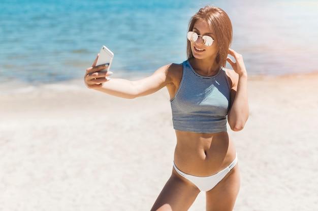 Lächelnde frau, die selfie nahe meer nimmt Kostenlose Fotos