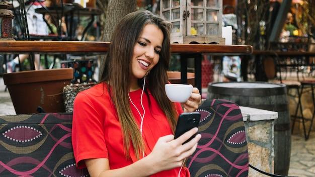 Lächelnde frau, die smartphone beim trinken des tasse kaffees verwendet Kostenlose Fotos