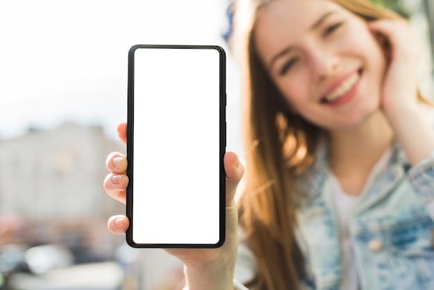Lächelnde frau, die smartphone des leeren bildschirms zeigt Kostenlose Fotos
