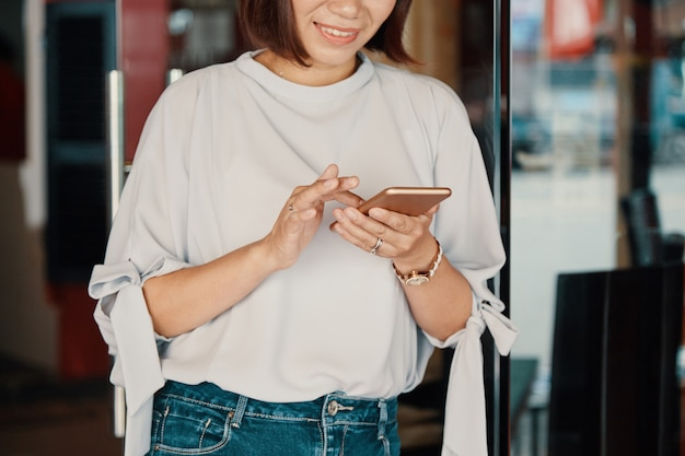 Lächelnde frau, die smartphone überprüft Kostenlose Fotos