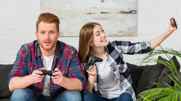 Lächelnde frau, die videospiel mit ihrem freund nimmt selfie auf smartphone spielt Kostenlose Fotos