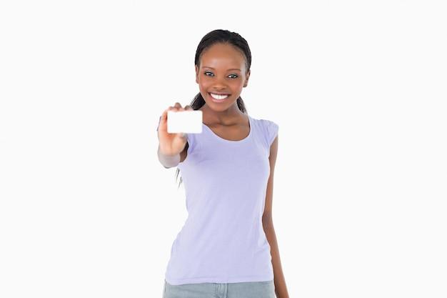 Lächelnde frau, die visitenkarte auf weißem hintergrund darstellt Premium Fotos