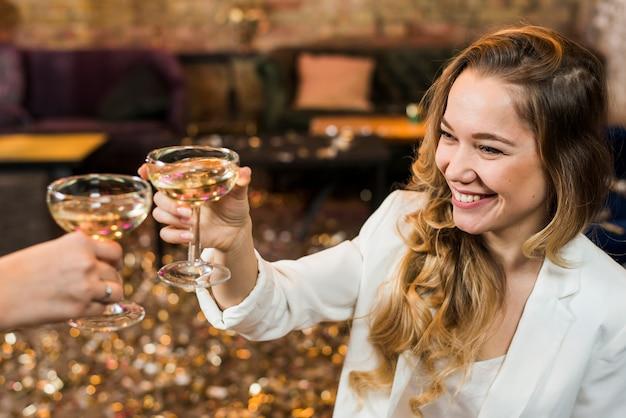 Lächelnde frau, die whisky mit ihrem freund in der partei röstet Kostenlose Fotos