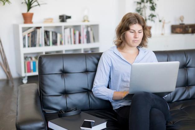 Lächelnde frau, die zu hause auf einem sofa unter verwendung eines laptops sitzt Premium Fotos