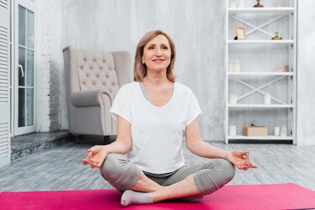 Lächelnde frau, die zu hause auf übendem yoga der yogamatte sitzt Kostenlose Fotos