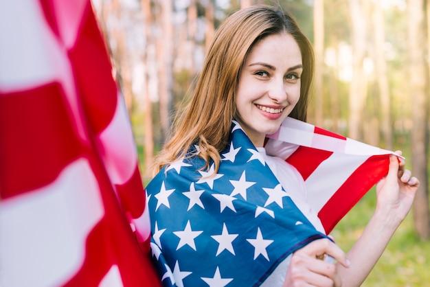Lächelnde frau eingewickelt in der nationalen amerikanischen flagge Kostenlose Fotos