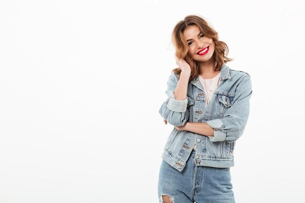 Lächelnde frau in der denimkleidung, die über weißer wand aufwirft Kostenlose Fotos