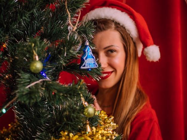 Lächelnde frau in sankt-hut hinter weihnachtsbaum Premium Fotos