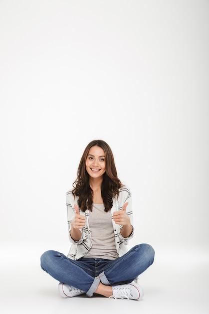 Lächelnde frau in voller länge in den jeans und in turnschuhen, die mit den beinen sitzen, kreuzte auf dem boden daumen oben gestikulierend, lokalisiert über weißer wand Kostenlose Fotos