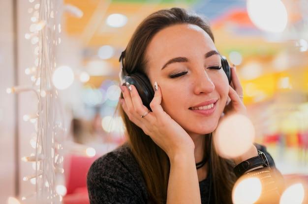 Lächelnde frau mit augen schloss das halten von kopfhörern auf kopf nahe weihnachtslichtern Kostenlose Fotos