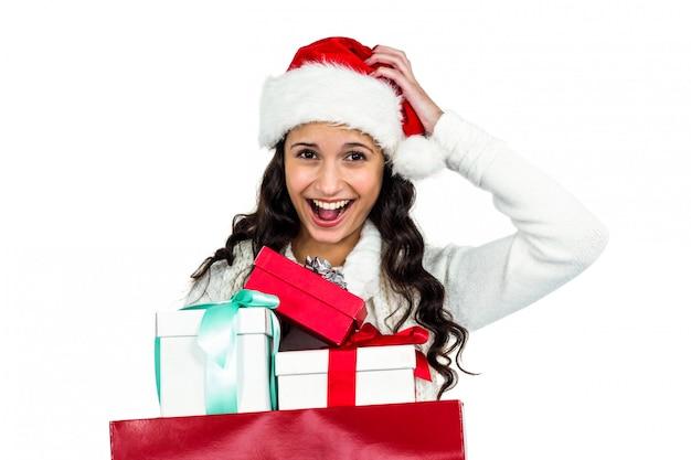 Lächelnde frau mit dem weihnachtshut, der geschenke hält Premium Fotos