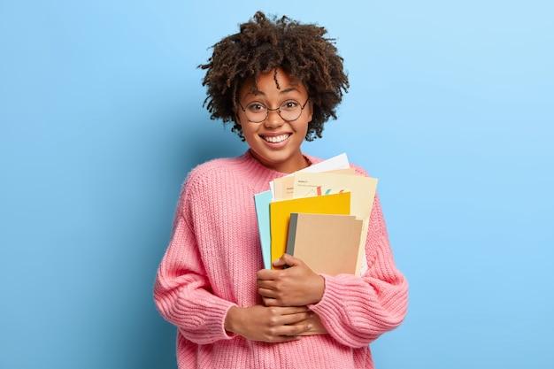 Lächelnde frau mit einem afro, der in einem rosa pullover aufwirft Kostenlose Fotos