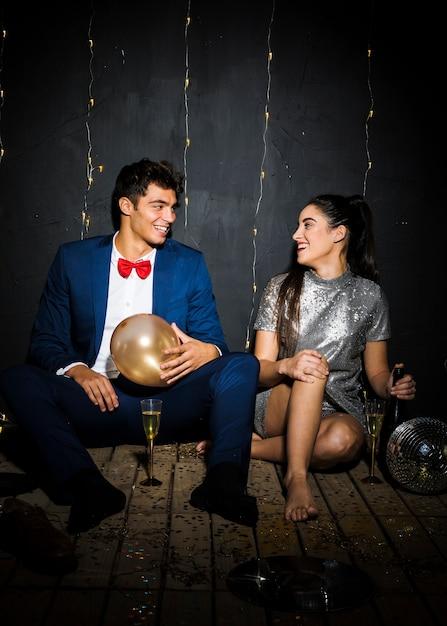 Lächelnde frau mit flasche nahe glücklichem mann mit ballon nahe gläsern Kostenlose Fotos
