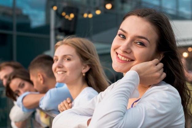 Lächelnde frau mit freunden im hintergrund Kostenlose Fotos