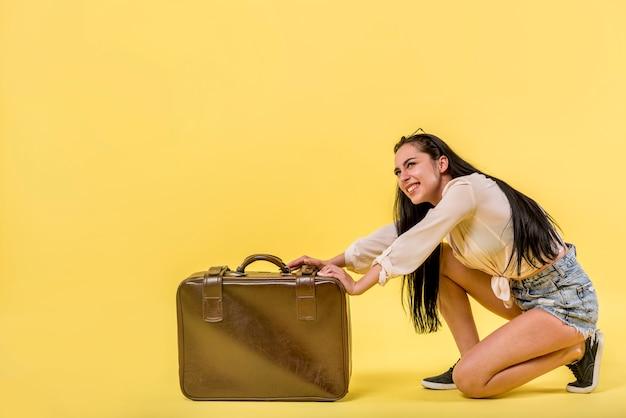 Lächelnde frau mit großem koffer Kostenlose Fotos
