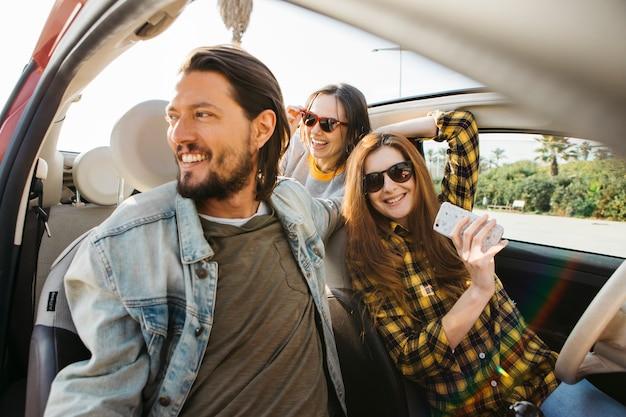 Lächelnde frau mit smartphone und positivem mann im auto nahe dame, die sich heraus vom auto lehnt Kostenlose Fotos