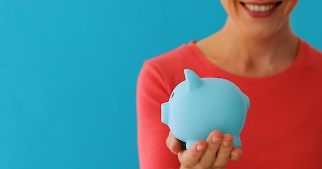 Lächelnde frau mit sparschwein Premium Fotos