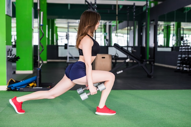 Lächelnde frau mit starkem körper macht verschiedene übungen im modernen sportclub mit spiegeln Kostenlose Fotos