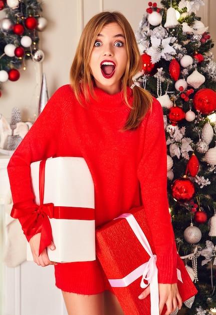 Lächelnde frau mit vielen geschenkboxen, die nahe geschmückten weihnachtsbaum aufwerfen Kostenlose Fotos