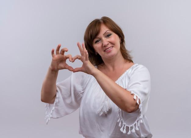 Lächelnde frau mittleren alters, die herzzeichen mit händen auf isolierter weißer wand zeigt Kostenlose Fotos