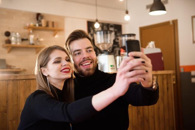 Lächelnde frau und gutaussehender mann, die kaffee, unter verwendung des handys beim verbringen von zeit in einer kaffeestube trinken. Premium Fotos