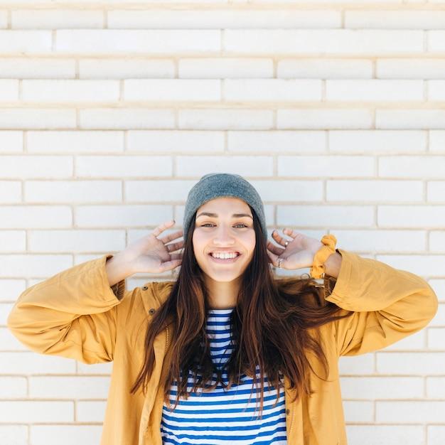 Lächelnde frau, welche die strickmütze und jacke stehen vor backsteinmauer trägt Kostenlose Fotos