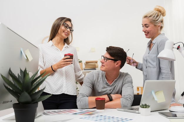 Lächelnde frauen, die mit mann im büro sprechen Kostenlose Fotos