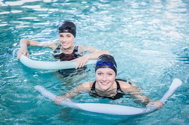 Lächelnde frauen im pool mit schaumstoffrollen im freizeitzentrum Premium Fotos
