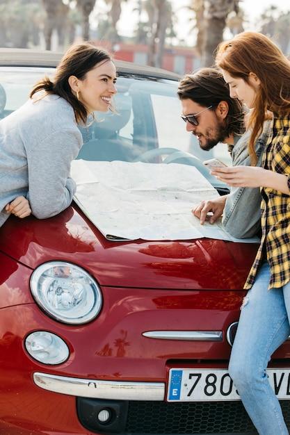 Lächelnde frauen mit smartphone nahe dem mann, der karte auf autohaube betrachtet Kostenlose Fotos