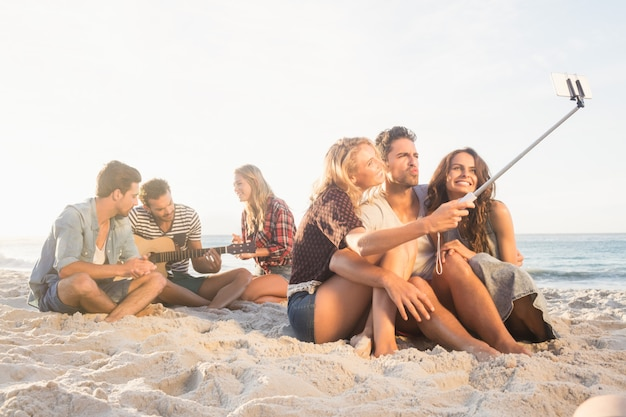 Lächelnde freunde, die auf dem sand singt und selfies nimmt sitzen Premium Fotos