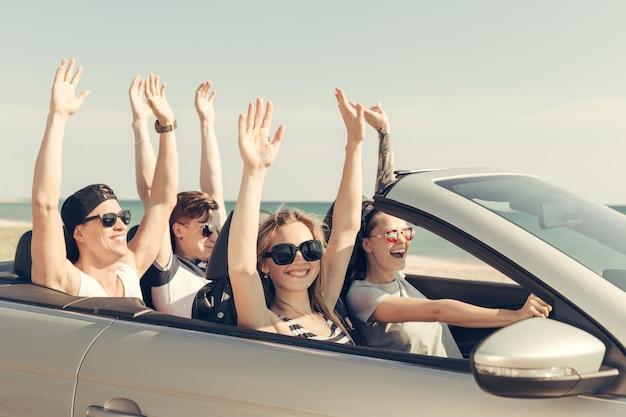 Lächelnde freunde, die auto nahe dem meer fahren und spaß haben Premium Fotos