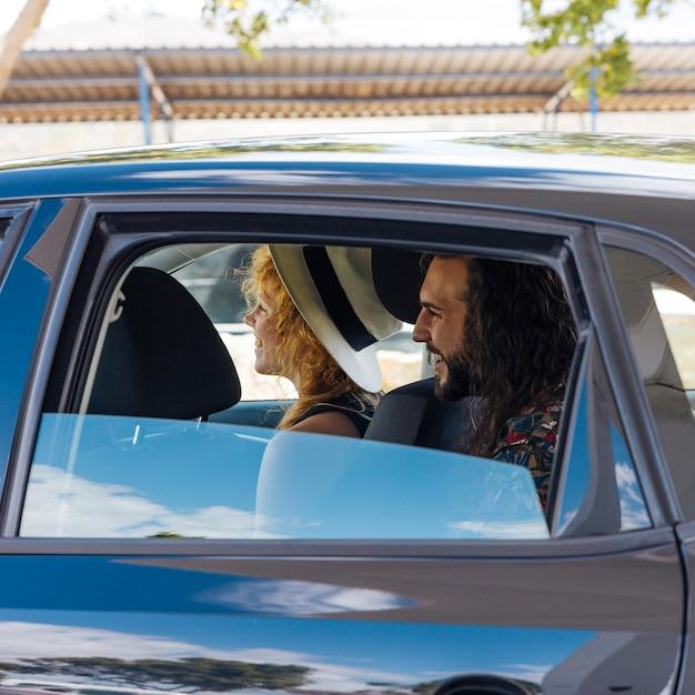 Lächelnde freunde, die im auto an der tankstelle sitzen Kostenlose Fotos