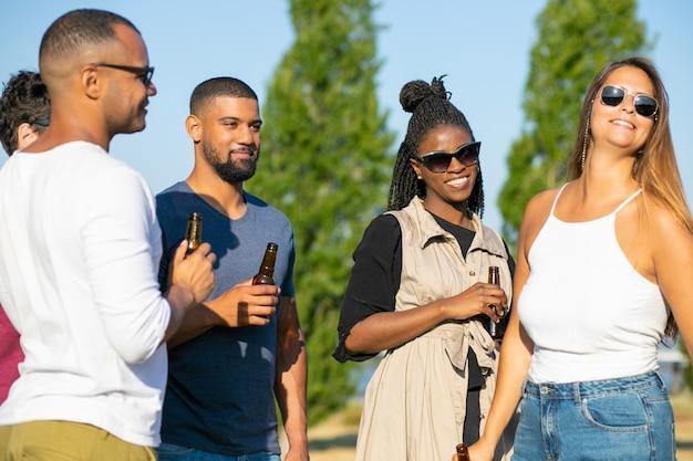 Lächelnde freunde, die mit bierflaschen während des feiertags stehen. gruppe junge leute, die während des sonnigen tages sich entspannen. freizeit Kostenlose Fotos
