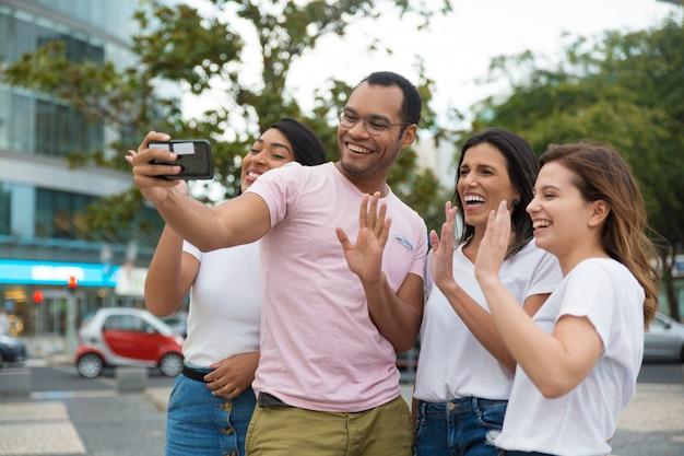Lächelnde freunde, die zum kameratelefon wellenartig bewegen Kostenlose Fotos