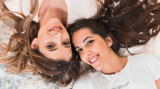 Lächelnde freundinnen, die auf federn liegen Kostenlose Fotos