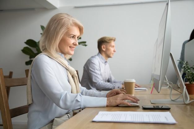 Lächelnde gealterte geschäftsfrau, die den computer online arbeitet in coworking büro verwendet Kostenlose Fotos