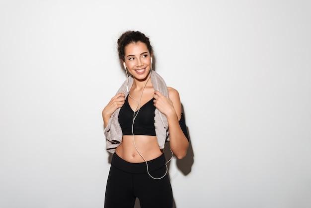 Lächelnde gelockte brunetteeignungsfrau mit hörender musik des tuches Kostenlose Fotos