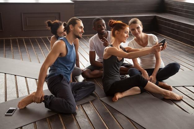 Lächelnde gemischtrassige leute, die selfie auf smartphone am yoga t machen Kostenlose Fotos