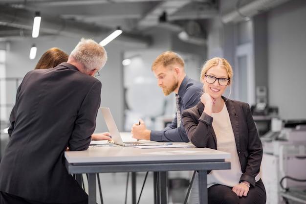 Lächelnde geschäftsfrau am arbeitsplatz während ihr kollege, der im büro sich bespricht Kostenlose Fotos