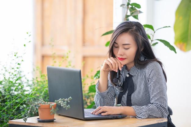 Lächelnde geschäftsfrau, die am laptop im café arbeitet Kostenlose Fotos