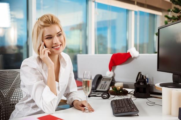 Lächelnde geschäftsfrau, die am telefon spricht, das im büroweihnachtstag arbeitet. Kostenlose Fotos