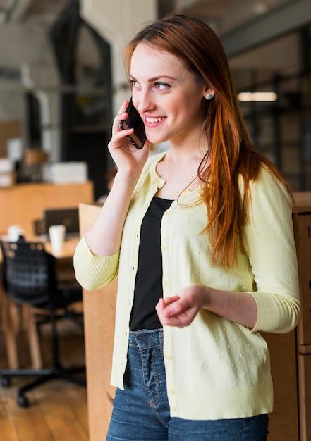 Lächelnde geschäftsfrau, die auf smartphone im büro spricht Kostenlose Fotos