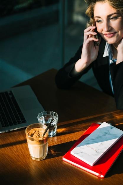 Lächelnde geschäftsfrau, die auf smartphone mit laptop spricht; schokoladenmilchshake und bücher über schreibtisch aus holz Kostenlose Fotos