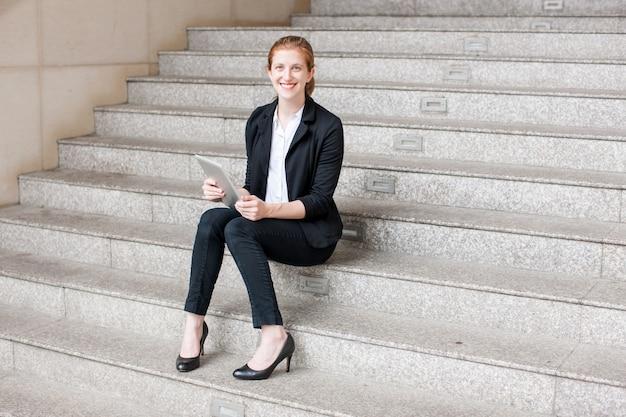 Lächelnde geschäftsfrau, die tablette auf treppe verwendet Kostenlose Fotos
