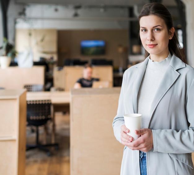 Lächelnde geschäftsfrau, die wegwerfkaffeetasse an arbeitsplatz hält Kostenlose Fotos
