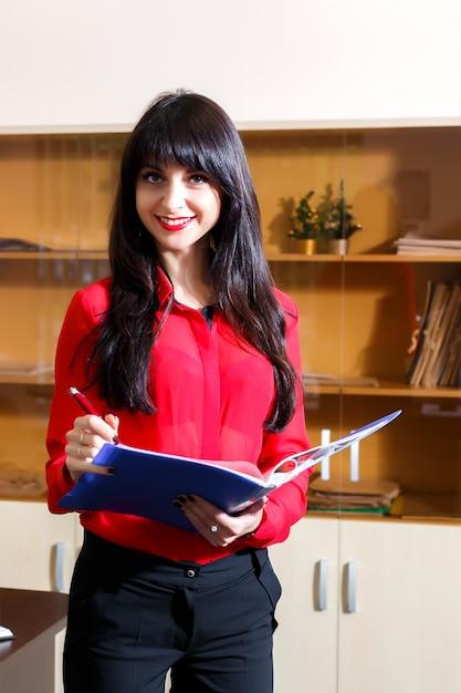 Lächelnde geschäftsfrau in einer roten bluse mit einem ordner von dokumenten im büro Premium Fotos